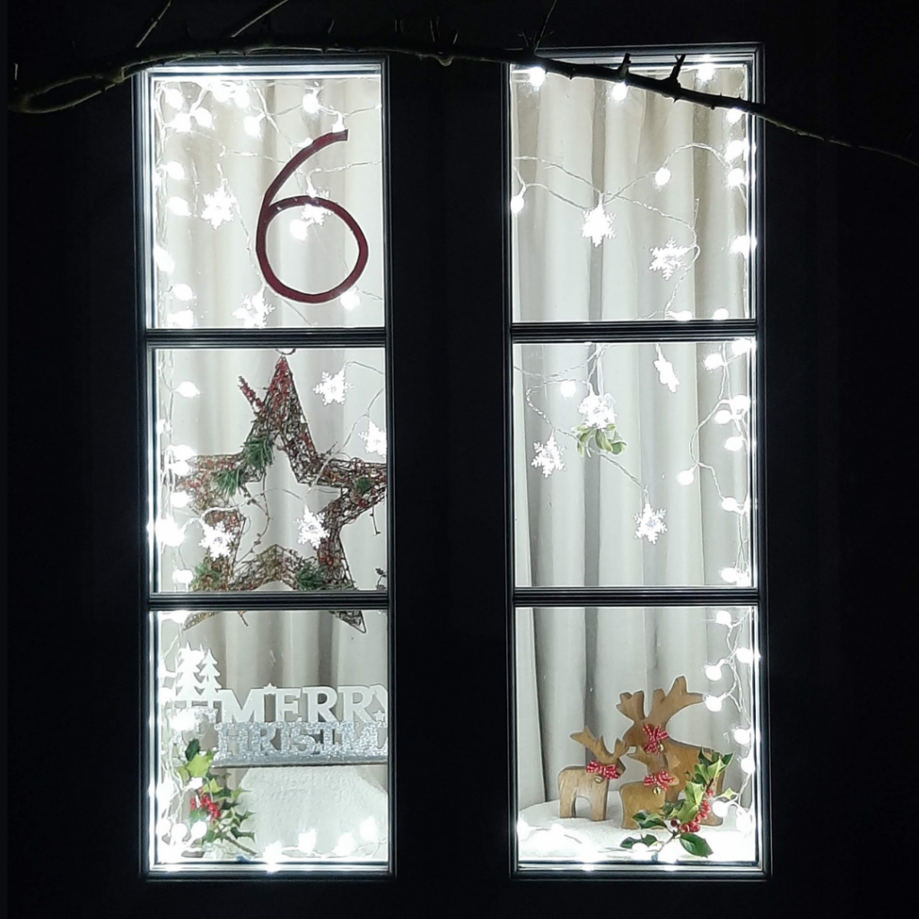 Close up of window 6, lit up with white fairy lights